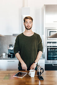 Portrait of man standing in kitchen raising his eyebrows