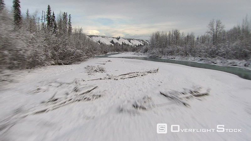 Flying low above icy river in Alaska