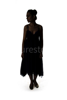 A Silhouette of woman in a summer dress, standing – shot from eye level.