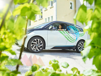 Smiling woman sitting in electric car