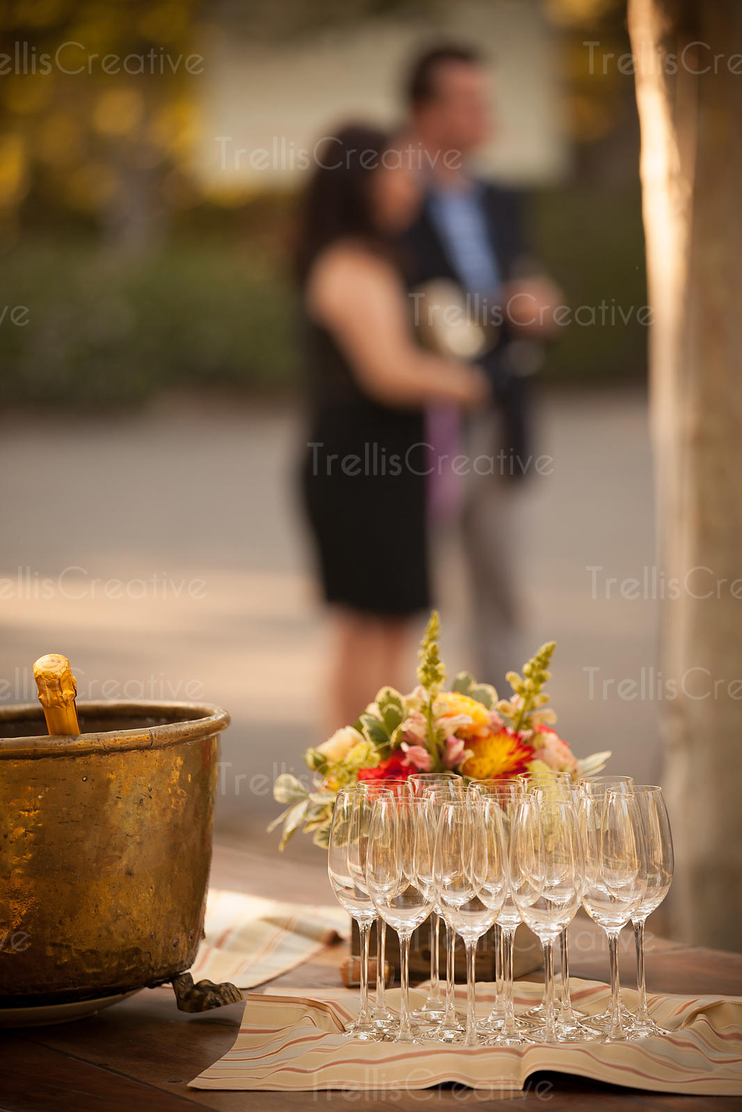 Table at a party with chilled champagne and sparkling wine glasses with people in background