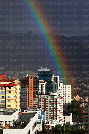 Rainbow over Sopocachi district and Muela del Diablo (a prominent rock outcrop overlooking the city) in rainy season, La Paz,...