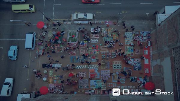 Top shot, colourful market on street corner with vehicles going past