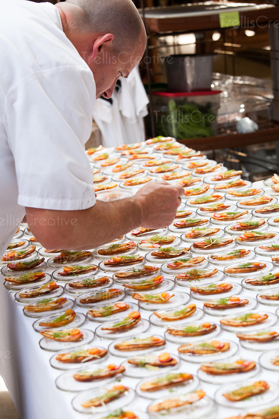 Chef putting the finishing touches on the savory crostini h'oderves ready for service at a party