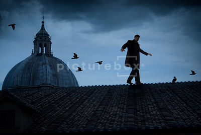 An atmospheric image of mystery man walking over the fooftops in Rome, Italy.
