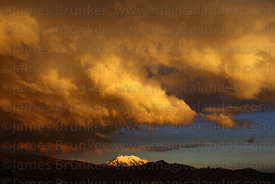 Dramatic rainy season storm clouds over Mt Illimani at sunset, Cordillera Real, Bolivia