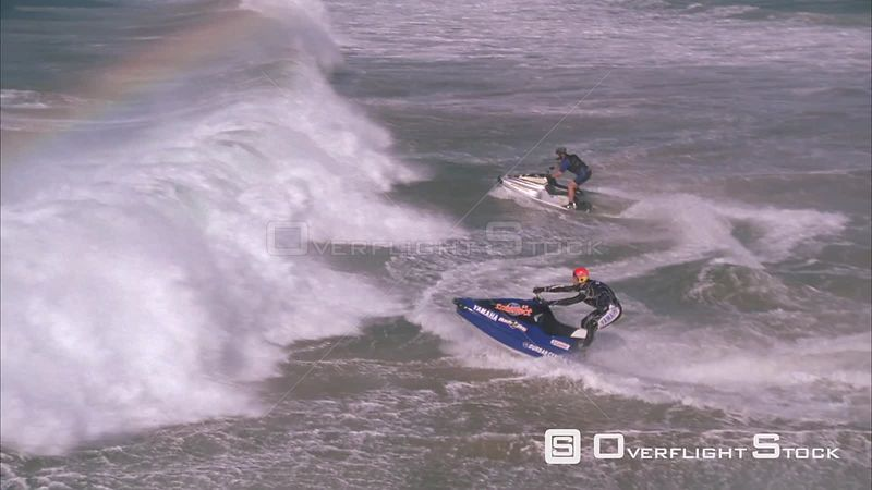 Slow motion pan of two jet skiers ramping a wave. KwaZulu Natal South Africa