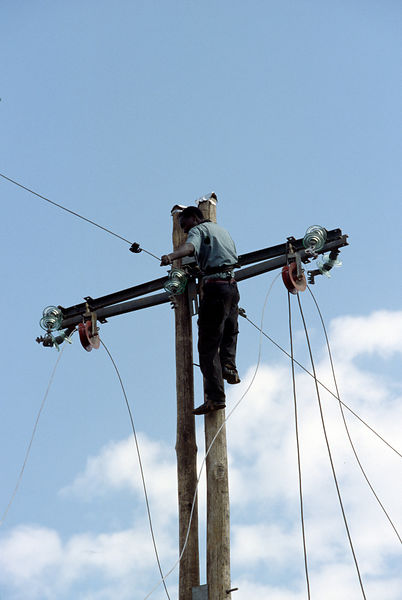 Burundi - Ruyigi - A workman repairs a telephone pole