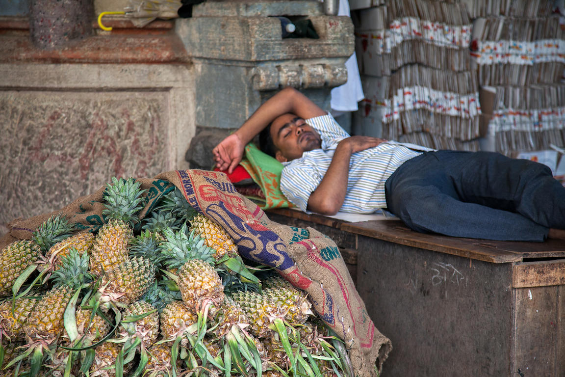 A worker sleeps next to a pile of pineapples at Crawford Market, Mumbai, India.