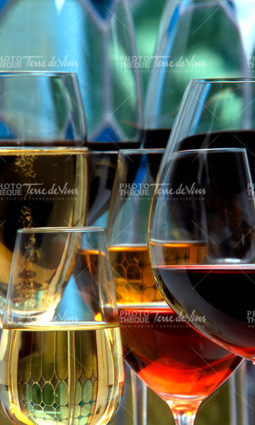 Champagne, white and red wins and drinks in glasses on stained glass background