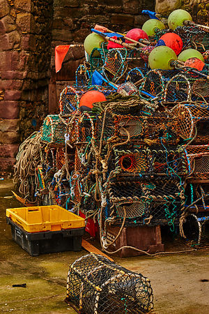Lobster pots stacked against a stone wall