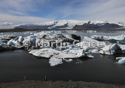 Icebergs in Jokulsarlon glacier lagoon, with two tourists in the foreground for scale, Austurland (Eastern Region, East Icela...