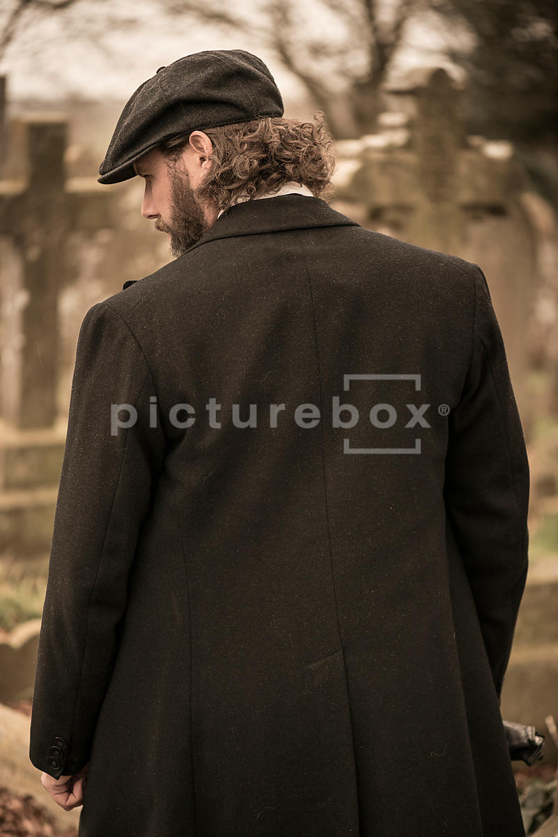 A vintage man in a peaky cap standing in a cemetery.