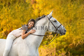 Girl smiling while hugging horse