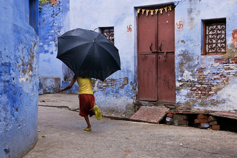 Boy Running in Alley with Umbrella