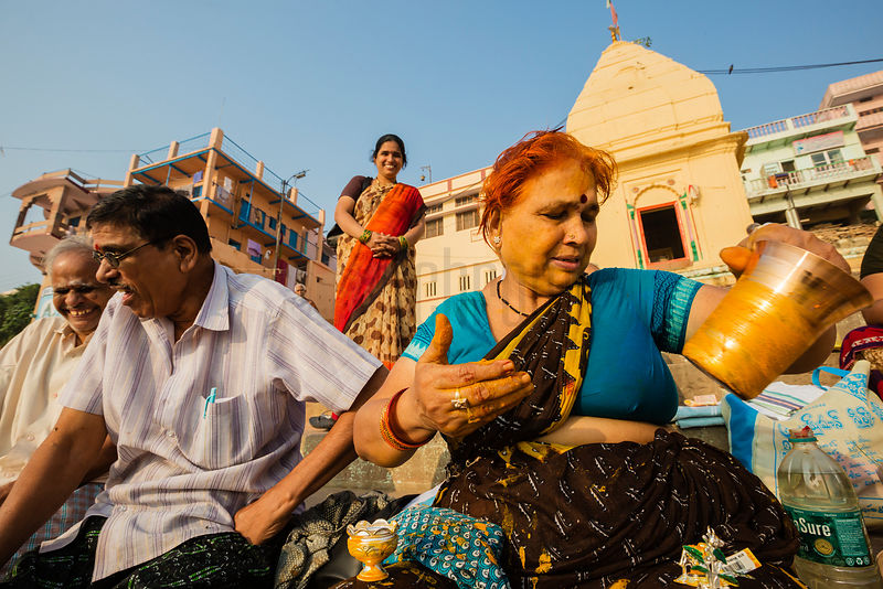 Woman Decorating a Brass Pot with a Turmeric Paste to be used in a Puja Ceremony on the Bank of the River Ganges