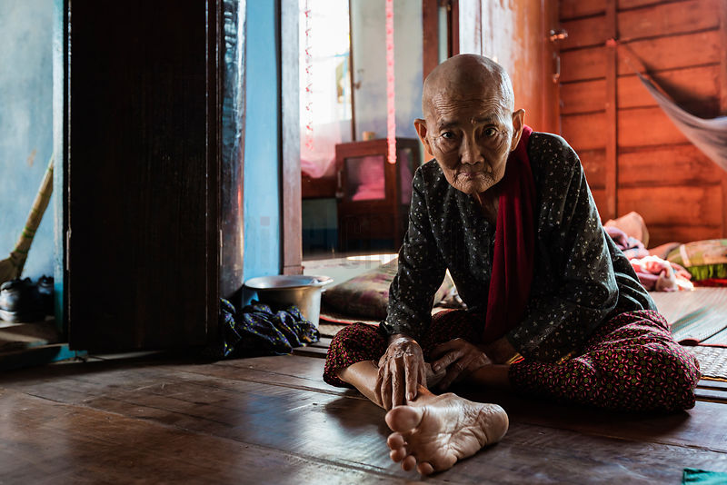 Portrait of an Elderly Woman Sitting on the Floor in her Home