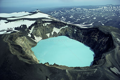 Aerial view looking down into blue sulphuric / hydrochloric lake in volcanic crater, Kamchatka, Russia