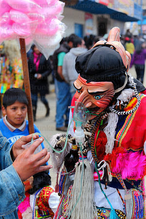 Masked Maqtas dancer drinking beer through a medical mask tube at Virgen del Carmen festival , Paucartambo , Peru