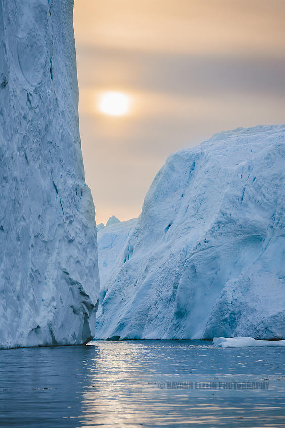 Sun rising between 2 large icebergs in calm water in the Unesco Ilulissat Icefjord in Greenland