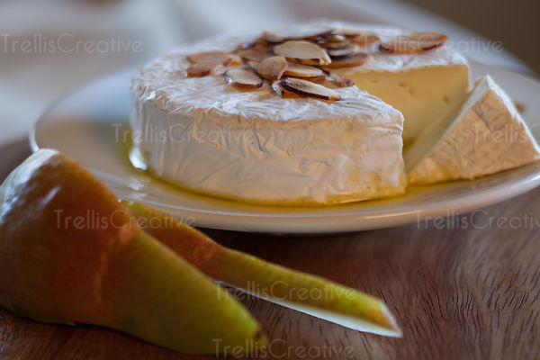 Slices of pears with roasted almond topped brie cheese wheel on a plate