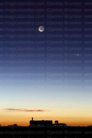 New moon with earthshine and Venus above old steam train in train cemetery at twilight, Uyuni, Bolivia