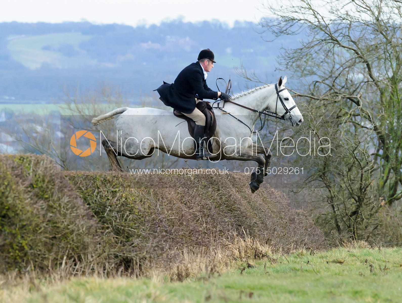 Shaun Cripps jumping a hedge above Wilson's covert
