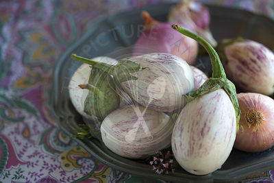 close up of plated white aubergines with purple fine stripes against purple floral tablecloth