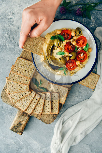 A woman dipping a cracker into a bowl of hummus without tahini topped with cherry tomatoes and green olives.