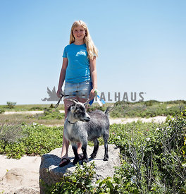 Blonde girl with pet goat standing on a rock at the Edgartown Beach