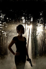 An atmospheric image of the silhouette of a mystery woman, standing in a misty, sunlit forest with a gun.