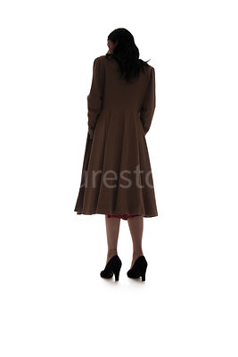 A silhouette of a 1940's woman in a coat, looking away – shot from low-level.