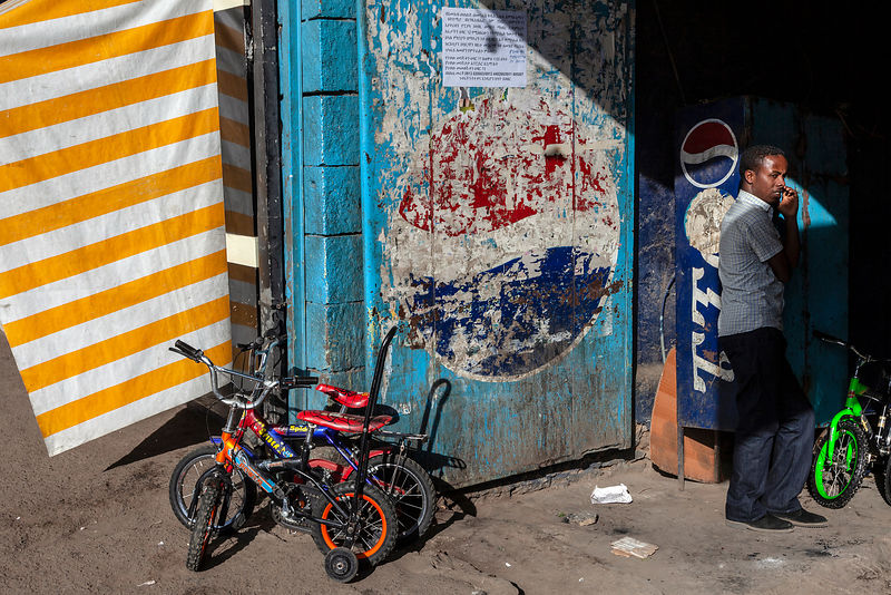 A man stands in the shadows by a doorway surrounded by children's bicycles