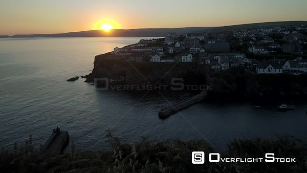 Drone flies over cliff towards the fishing village of Port Isaac in Cornwall as the sun rises
