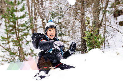 Happy boy playing with snow in the woods