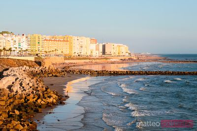 City and beach at sunset, Cadiz, Andalusia, Spain