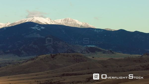 The early morning sunrise highlights the snow-covered peaks of the Gravelly mountain Range near Ennis, Montana