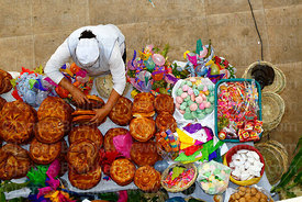 Woman arranging loaves of bread on stall selling items for decorated baskets during Comadres festival, Tarija, Bolivia