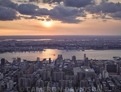 Aerial photograph of Midtown Manhattan and the Hudson River at sunset.