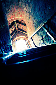 An atmospheric image of sunlight coming through a door, at the top of some cellar steps, in an old building.