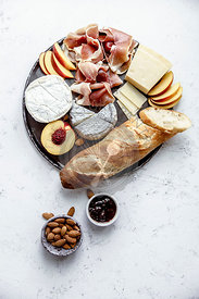 Cheese and ham plate with parmesan, camamber, goat cheese, ham and snacks. Overhead view, white textured background