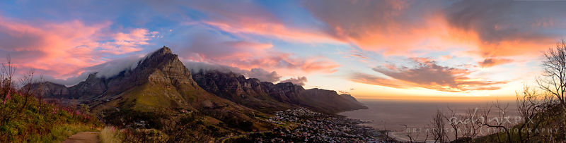 Panoramic view of Table Mountain and the Twelve Apostles above Camps Bay, with pink clouds lit by the setting sun, viewed fro...