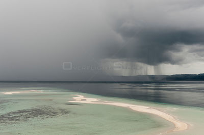 Sand cay and approaching rainstorm over the sea. Raja Ampat, West Papua, Indonesia, February 2010