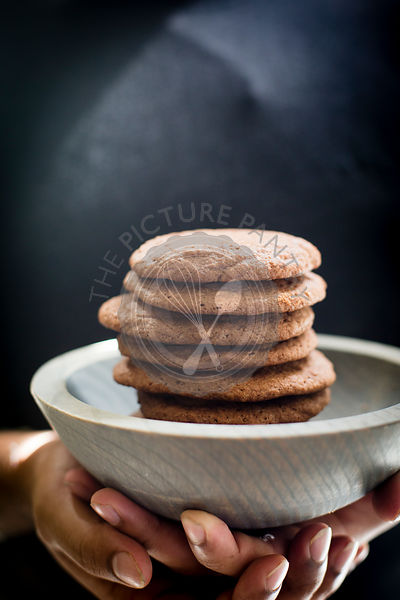 Stack of Brownie cookies in a grey wooden bowl model hands on shot