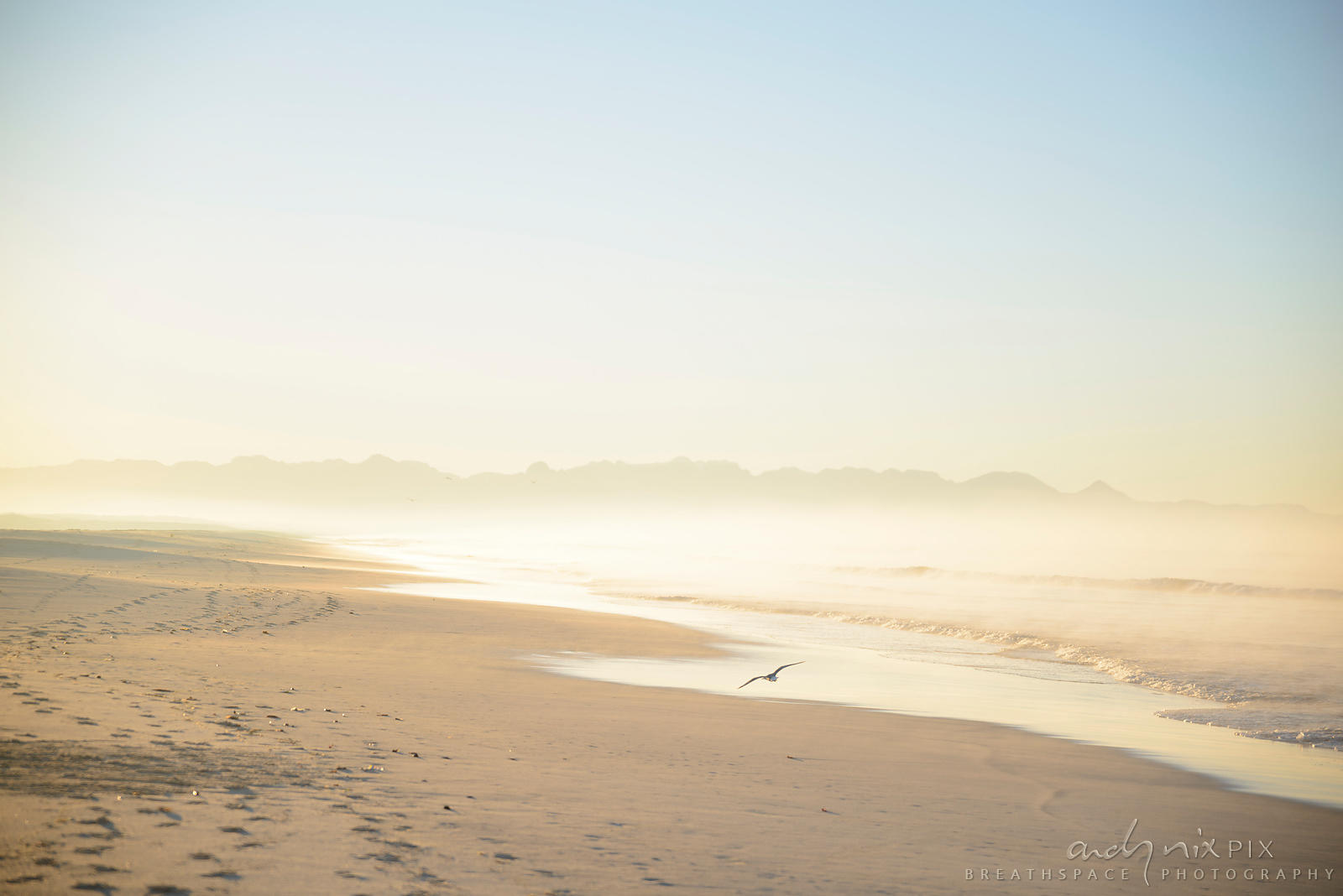 Mist rising from the sand and waves on the beach at sunrise