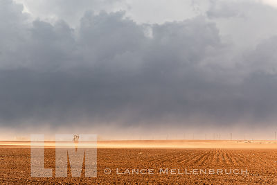 Wind blowing dust over plowed field with oil rig in Texas