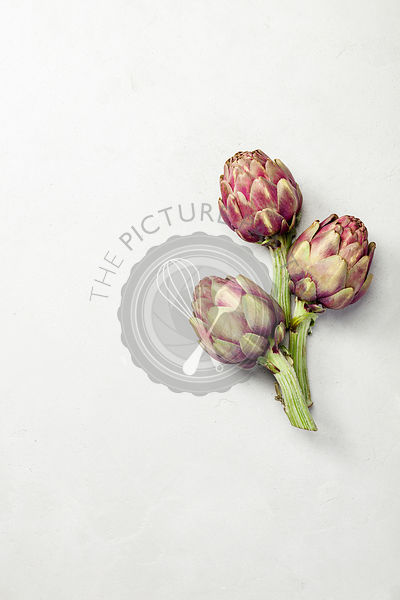 Top view of artichokes on concrete background