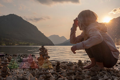 Austria, Ausseer Land, Girl building cairns at lakeshore