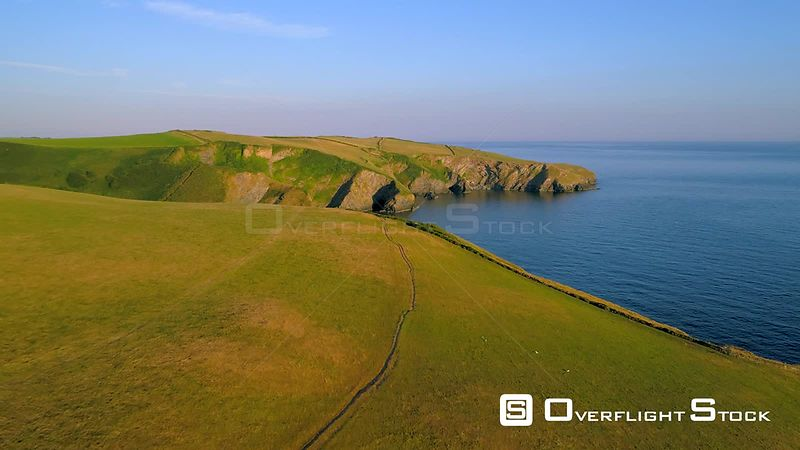 Drone camera flies over stunning headland and cliffs near Port Isaac in Cornwall during the golden hour