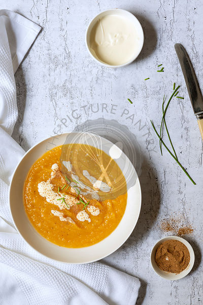 A bowl of thick homemade pumpkin soup with small bowls of cream and nutmeg and chives.